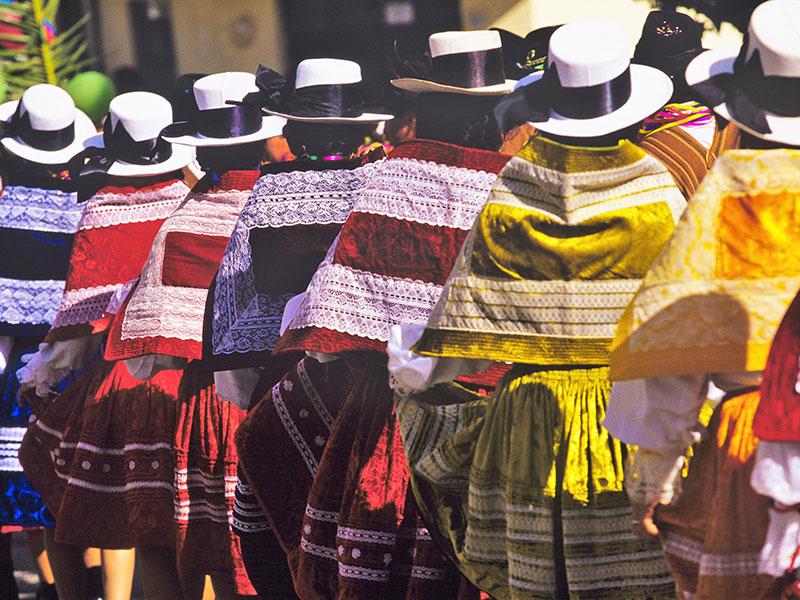 Vrouwen in schitterende klederdracht ziet u overal op reis in Peru en Ecuador.