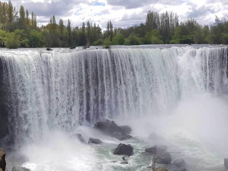 Een foto van een waterval en de groene natuur in Chili