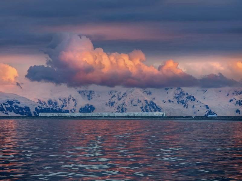 De mooie wolken met een oranje vloed en water op de voorgrond