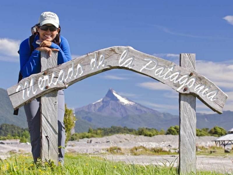 Een wandelaar die met een bord van Patagonië op de foto staat